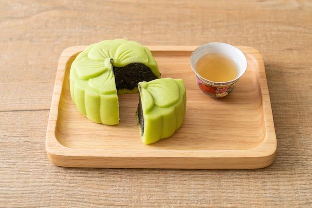 Chinese maancake groene thee smaak met thee op houten plaat