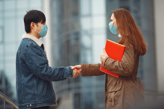 Chinese man en een vrouw in wegwerpmaskers schudden handen