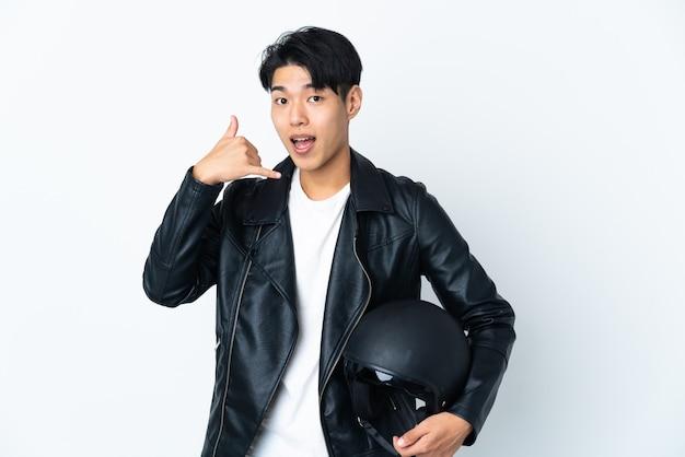 Chinese man met een motorhelm op wit telefoongebaar maken. bel me terug teken