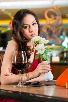 Chinese nerveuze, hoopende, eenzame, dromerige, hartverscheurende vrouw in een restaurant wachtend op een date stond op