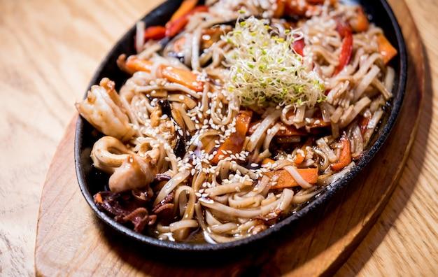 Chinese noedels met mosselen en garnalen op de houten tafel.
