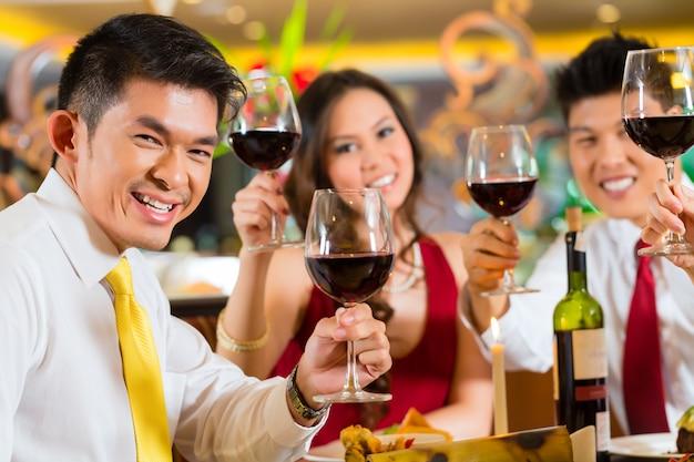 Chinese paren die met wijn in restaurant roosteren