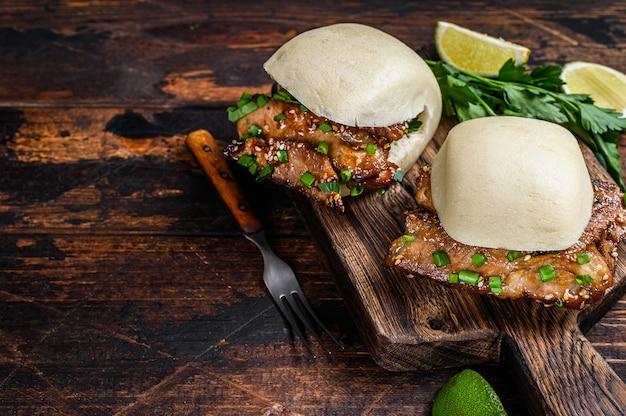 Chinese sandwich gestoomde gua bao-broodjes met varkensvlees. zwarte achtergrond. bovenaanzicht. kopieer ruimte.