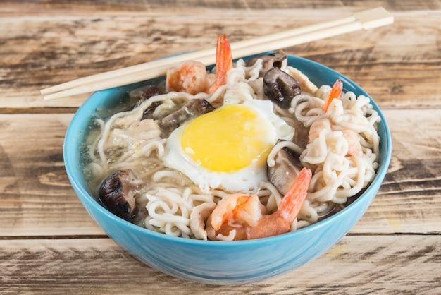 Chinese soep met udon noedels varkensvlees gekookte eieren, champignons en garnalen close-up in een kom op tafel