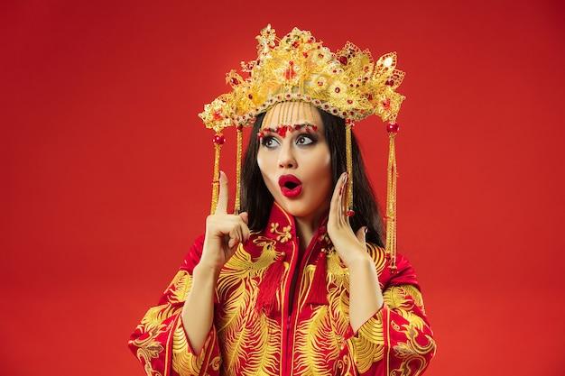Chinese traditionele bevallige vrouw bij studio over rode achtergrond. mooi meisje dat klederdracht draagt. chinees nieuwjaar, elegantie, gratie, performer, performance, dans, actrice, jurkconcept