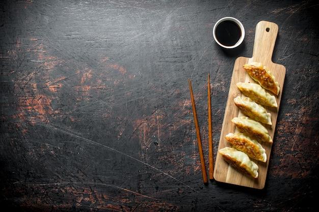Chinese traditionele gedza-dumplings op houten snijplank op donkere rustieke tafel.
