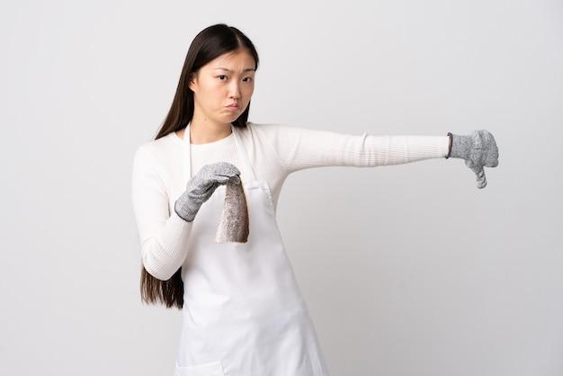 Chinese visboer die een schort draagt en een rauwe vis over wit houdt met duim omlaag met een negatieve uitdrukking