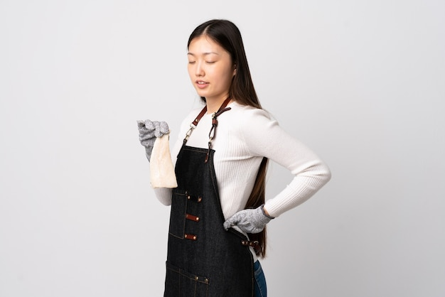 Chinese visboer die een schort draagt en een rauwe vis vasthoudt over geïsoleerde witte achtergrond die aan rugpijn lijdt omdat hij zich heeft ingespannen