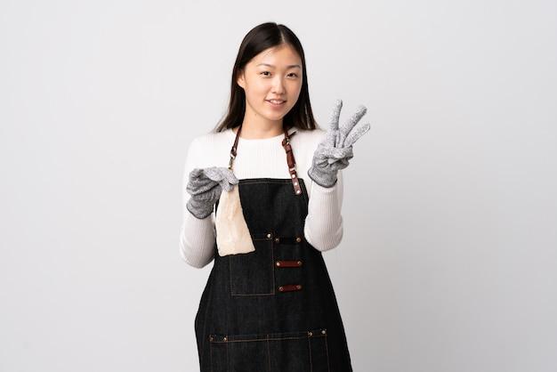 Chinese vishandelaar die een schort draagt en een ruwe vis over geïsoleerde witte muur gelukkig houdt en drie met vingers telt
