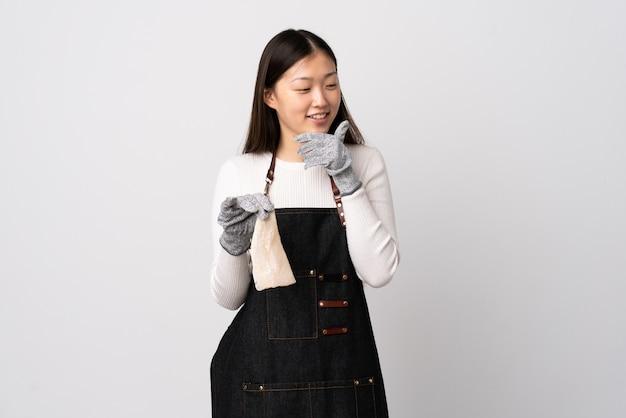 Chinese vishandelaar die een schort draagt en een ruwe vis over geïsoleerde witte muur houdt kijkend aan de kant en glimlachend
