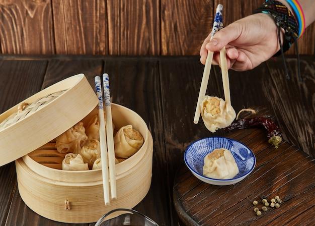 Chinese vleesknoedels gestoomd in een bamboestoomboot en een met de hand geplukte knoedels met stokjes