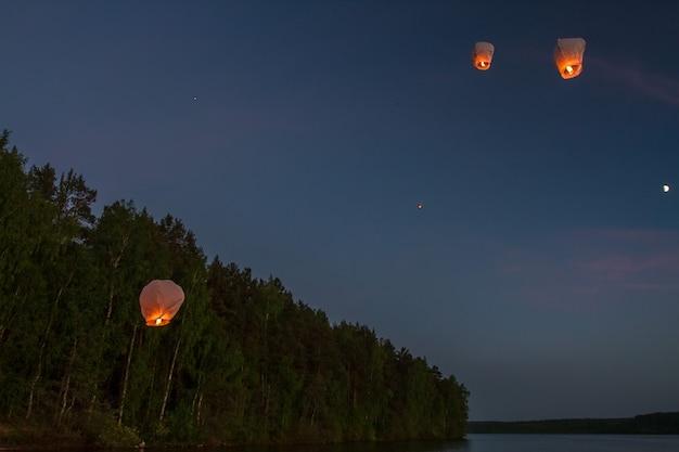 Chinese vliegende lantaarns die in het donker over het meer vliegen