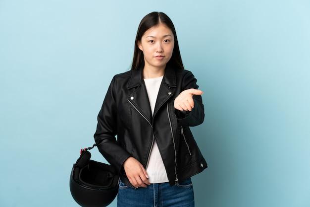 Chinese vrouw die een motorfietshelm over blauw muurhandenschudden houdt na veel