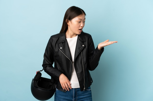 Chinese vrouw die een motorfietshelm over blauwe muur houdt die lege ruimte denkbeeldig op de palm houdt