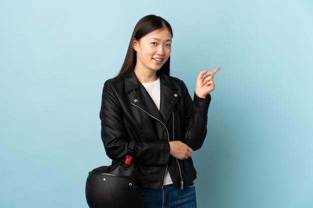 Chinese vrouw die een motorfietshelm over geïsoleerde blauwe wijzende vinger aan de kant houdt