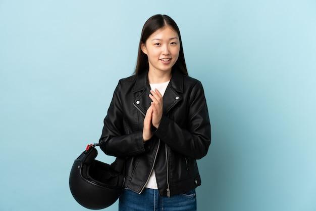 Chinese vrouw die een motorfietshelm over het geïsoleerde blauwe toejuichen houdt
