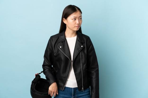 Chinese vrouw die een motorhelm over geïsoleerde blauwe muur houdt die kant kijkt