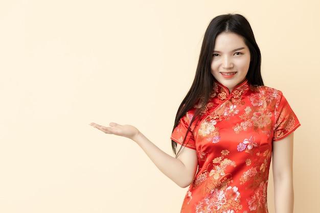 Chinese vrouw die een product presenteert, traditionele kleding van qipao kleedt.