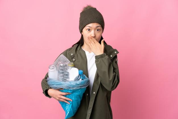 Chinese vrouw die een zakhoogtepunt van plastic flessen houdt om over geïsoleerde roze muur te behandelen mond met handen te recycleren