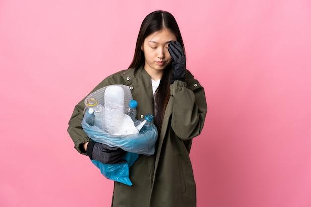Chinese vrouw die een zakhoogtepunt van plastic flessen over geïsoleerde roze muur met hoofdpijn te recycleren
