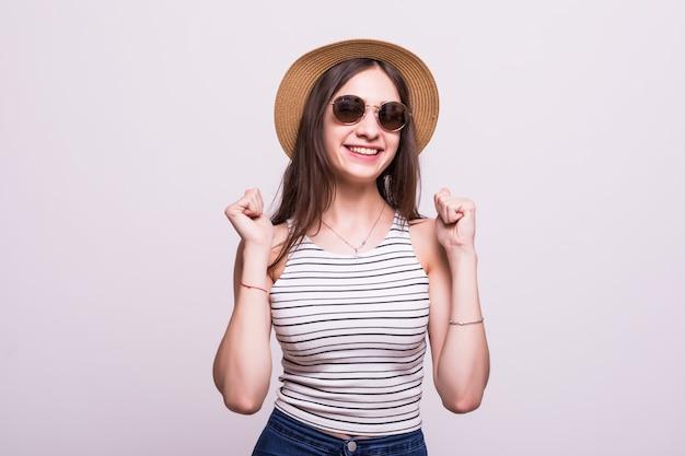 Chinese vrouw die hoedenzonnebril dragen die zich over geïsoleerde witte achtergrond bevinden die verrast en verbaasd voor succes met opgeheven wapens en open ogen vieren. winnaar concept.