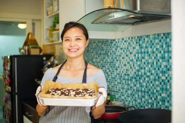 Chinese vrouw die verse brownieschocolade houdt nadat ze klaar was met koken