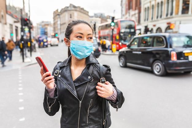 Chinese vrouw in londen die gezichtsmasker draagt om tegen smog en virus te beschermen