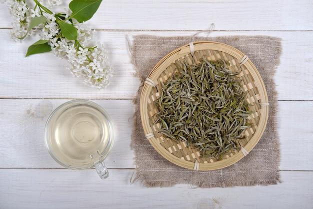 Chinese witte thee in bamboeschotel en witte lila bloemen op houten achtergrond