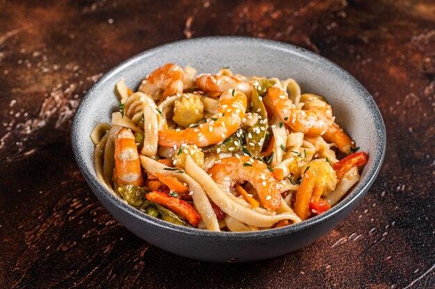 Chinese wok roerbak udon zeevruchtennoedels met garnalen in een kom.