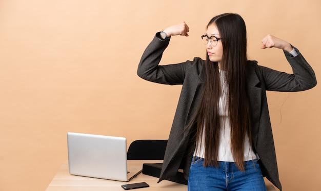 Chinese zakenvrouw in haar werkplek sterke gebaar doen