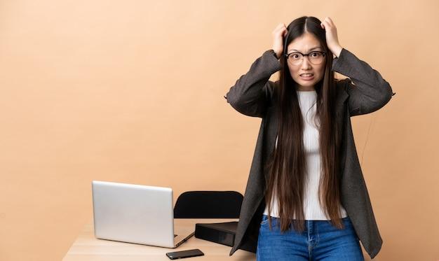 Chinese zakenvrouw in haar werkplek zenuwachtig gebaar doen