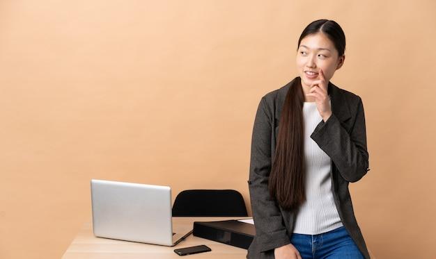 Chinese zakenvrouw op haar werkplek die een idee denkt terwijl ze omhoog kijkt