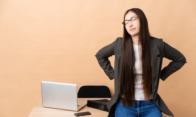 Chinese zakenvrouw op haar werkplek die lijdt aan rugpijn omdat ze zich heeft ingespannen