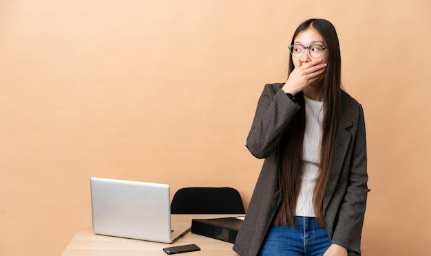 Chinese zakenvrouw op haar werkplek doet verrassingsgebaar terwijl ze naar de zijkant kijkt