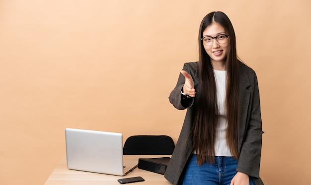 Chinese zakenvrouw op haar werkplek handen schudden voor het sluiten van een goede deal