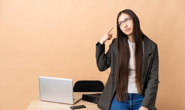 Chinese zakenvrouw op haar werkplek, het gebaar van waanzin maken vinger op het hoofd