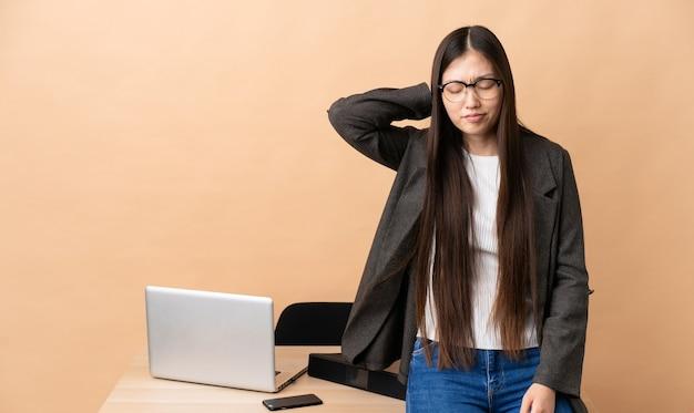Chinese zakenvrouw op haar werkplek met nekpijn