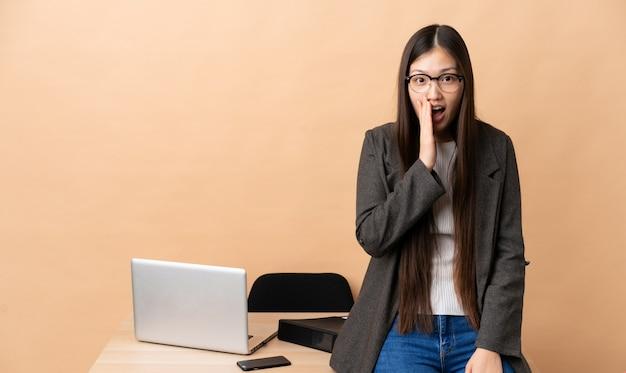 Chinese zakenvrouw op haar werkplek met verrassing en geschokte gelaatsuitdrukking