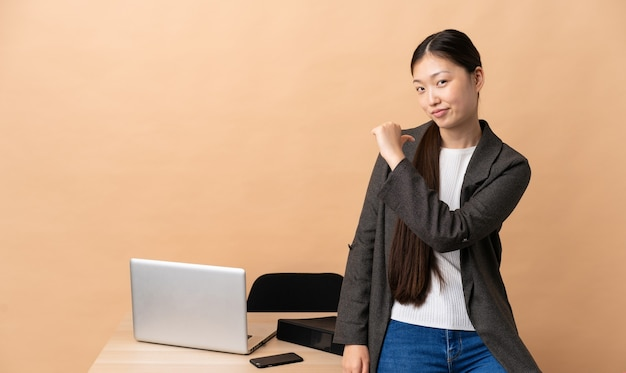 Chinese zakenvrouw op haar werkplek, trots en zelfvoldaan