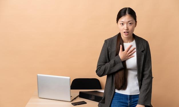 Chinese zakenvrouw op haar werkplek verrast en geschokt terwijl ze goed keek