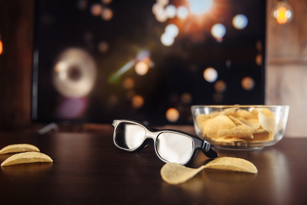 Chips en 3d-bril aan het bureau voor een grote tv.