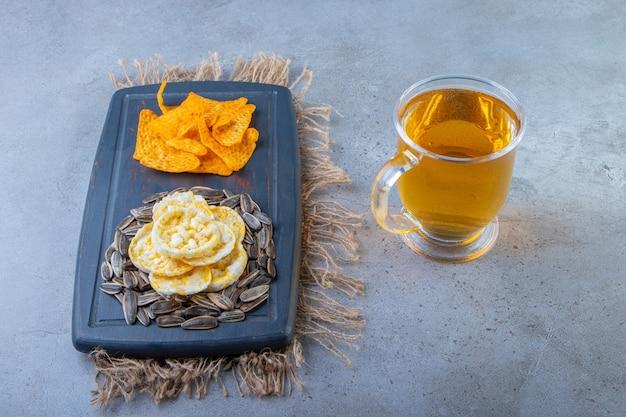 Chips en zaden op een dienblad op een jute servet naast glas bier, op het blauwe oppervlak.