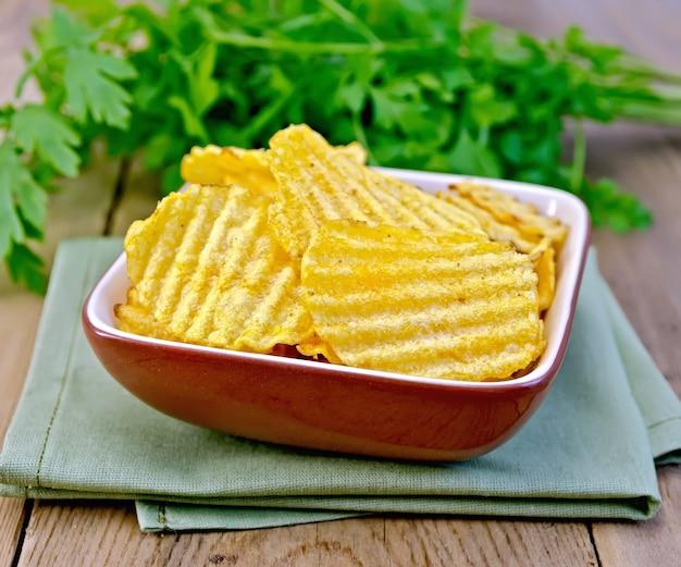 Chips gegroefd in een klei kom op een servet, peterselie op een houten planken achtergrond