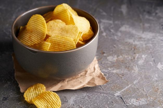 Chips in een grijze kom op een grijze achtergrond