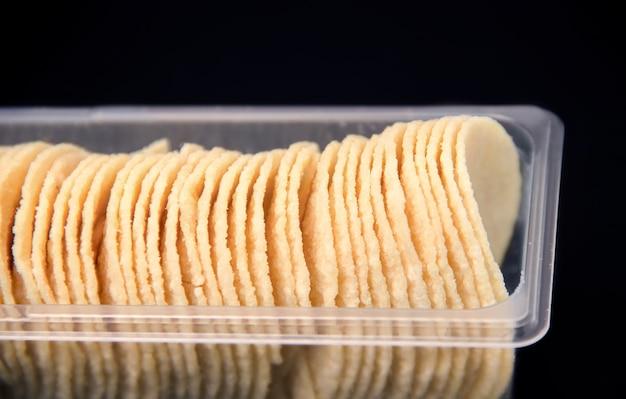 Chips in een lang pakket op een zwarte achtergrond close-up