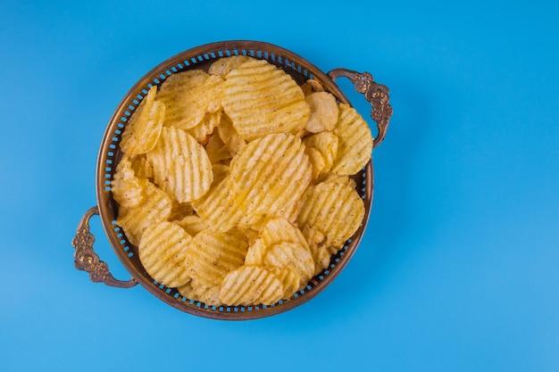 Chips in zilveren kommen op blauw.