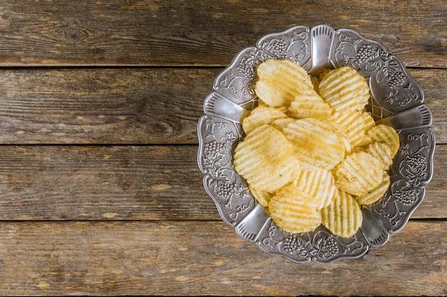 Chips in zilveren uitstekende plaat op houten achtergrond.