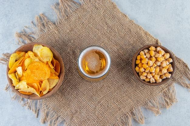 Chips kikkererwten en bierglas op een jute servet, op het marmeren oppervlak.