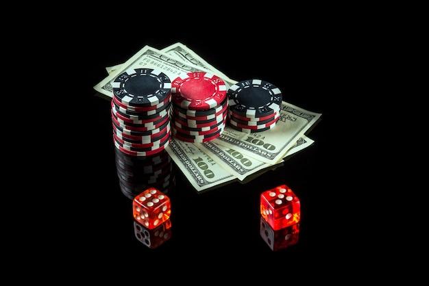 Chips met dollars en dobbelstenen op een zwarte achtergrond