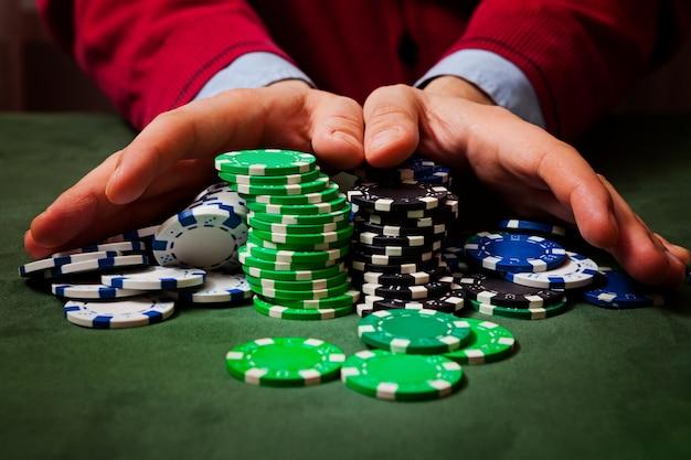 Chips op de voorgrond, in het vervagen van de handen van een man die chips vasthoudt, poker speelt
